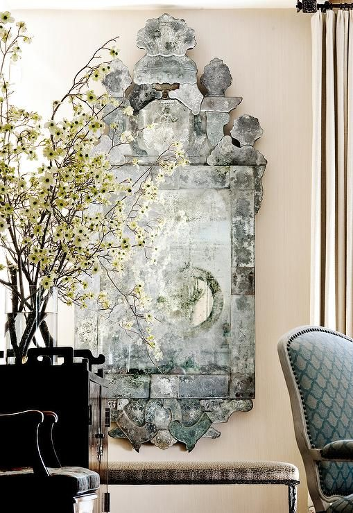 Bringing out the colors a blue arabesque print chair, a stunning antiqued Venetian mirror is mounted on tan textured walls beside long tan curtains and above a cheetah print bench positioned adjacent to a black chinoiserie chest topped with a large glass flower vase.