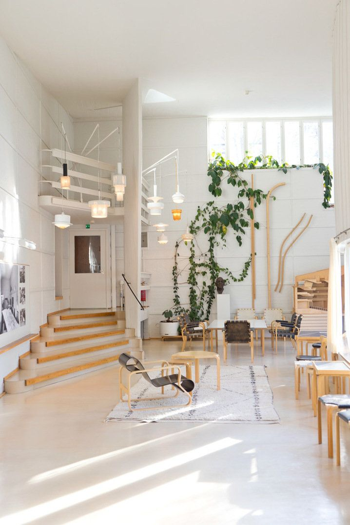 The incredible studio space of designer Alvar Aalto in Helsinki with curving main space, high ceilings drenched with light and trailing plant wall.