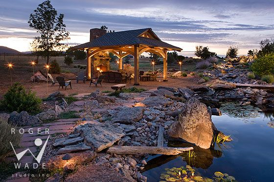 timber frame pavilion with fireplace and landscaped pond and water feature at twilight