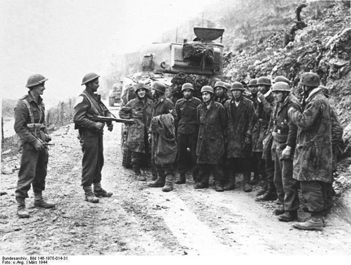 Two New Zealand soldiers guarding a group of German prisoners of war Monte Cassino Italy March 1944.