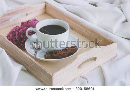 Wooden tray with a cup of coffee and cookies on a bed