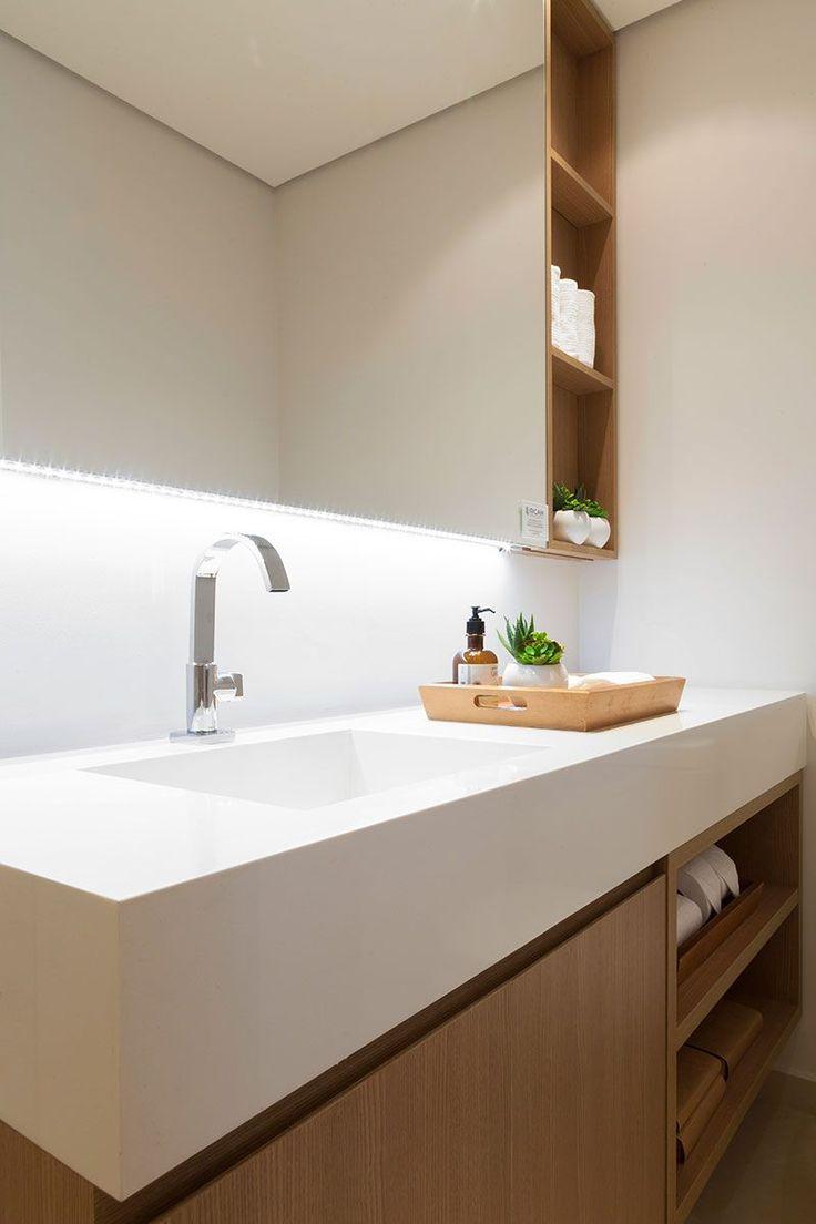 Decoração de apartamento pequeno e charmoso com ambientes integrados com ripas de madeira. No banheiro, lavabo, cuba branca, bandeja de madeira, nicho de planta com plantas e armário de madeira.
