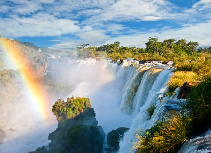 Iguazu Falls Argentina Iguazu National Park, which is situated on the international border of Argentina and Brazil, features one of the world's most breathtaking natural wonders. The Iguazu Falls is a majestic sight of roaring water with rainbows adorning the cascades. You can get up close to these falls by walking one of the wooden walkways that stretch out over the river.