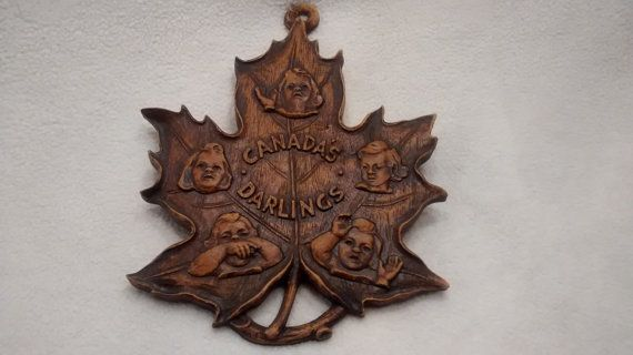 Dionne quintuplets maple leaf made of wood for sale by TheresasTimeMachine. It is in extremely good condition except for a small crack in the loop.