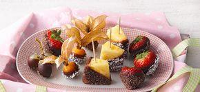 Rezept für Früchte mit Kakao-Kokos-Glasur: 1. Erdbeeren und Weintrauben waschen und abtropfen lassen. Jeweils 2-3 Weintrauben  vom Stiel lösen. Physalisblätter nach hinten aufbiegen und hochdrehen, Physalis  vorsichtig waschen und trocken tupfen. Ananas schälen, vierteln und Strunk herausschneiden.  In mundgerechte Stücke schneiden. Holzspieße in die Früchte stecken.  2. Kokosöl in einen kleinen Topf geben und bei niedriger Hitze schmelzen. SweetFamily  Kakao-Puderzucker zufügen, gut…