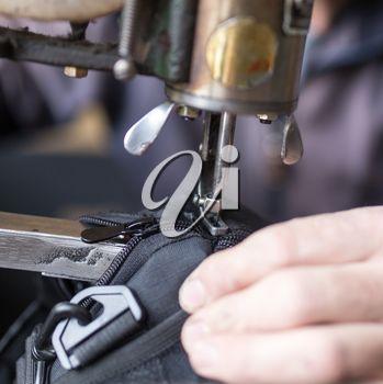 Tailor man sews up a bag in a workshop .