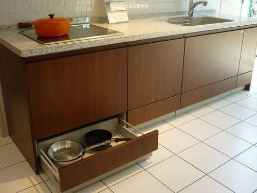 面材の分割が少なく取手のないすっきりしたキッチンキャビネット 下段は足入れ部分に手をかける造り