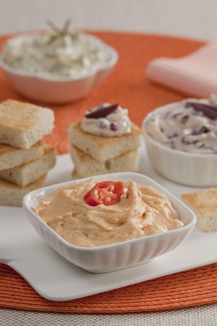 Em uma tigela, misture bem os queijos, o azeite, o creme de leite e o sal até formar uma pasta. Divida a pasta em três partes. Em uma delas, misture a páprica. Na segunda, misture as azeitonas. Na …