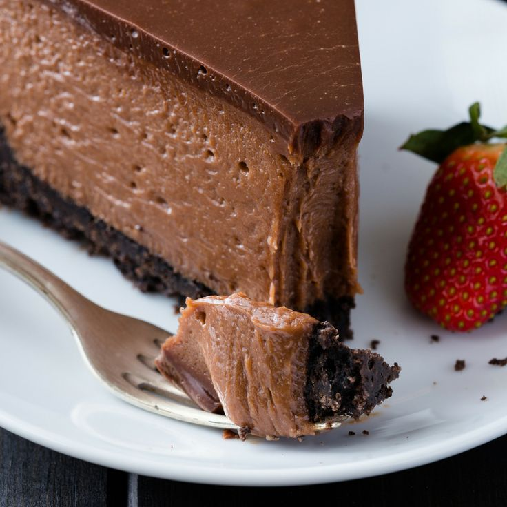 Nutella Cheesecake Recipe that is so decadent and creamy! It rests on an oreo crust and is covered in a Nutella glaze. #bakedbyanintrovertrecipes #nutella #cheesecake #oreocrust