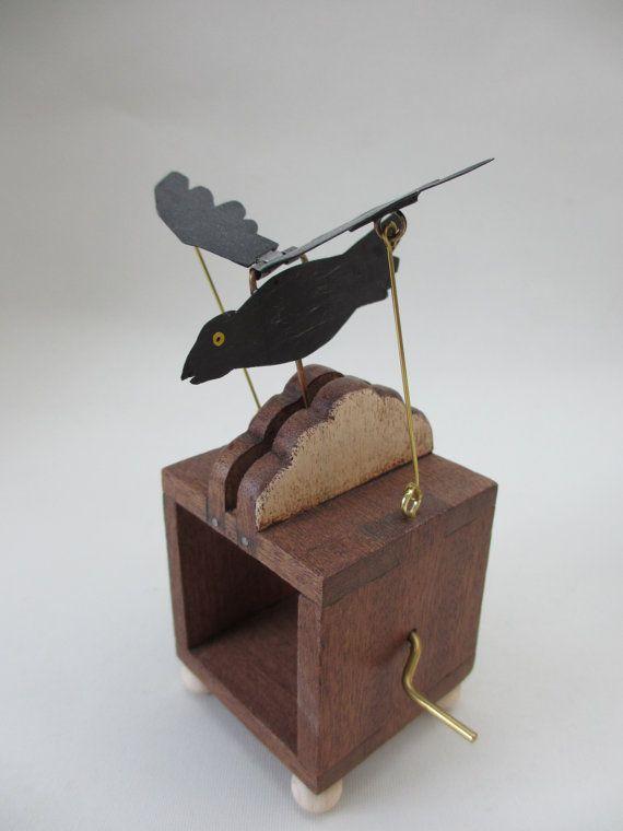 Este autómata dispone de mano cortó y Cuervo de hojalata pintados de mano que aletea sus alas por encima de la nube cuando la manija se da vuelta.  La caja y la nube se hacen de la madera y el mango es de latón. La caja ha sido terminada con una cera para muebles.  Nota: Esto no es un juguete y no es adecuado para el uso de los niños.  El tamaño del autómata de cuervo de vuelo es de aproximadamente: 12cm de alto (en su punto más alto) x 7,5 cm de profundidad (incluyendo la manija) x 5cm…