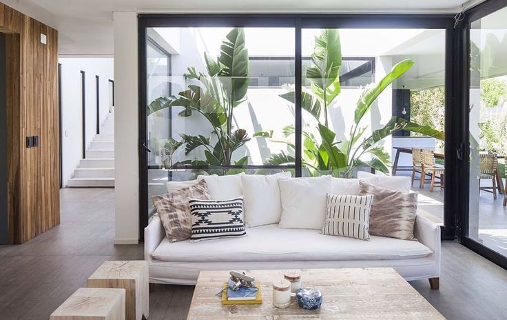 What a clever #design! The team at Estudio PKA. / Pessagno Kandus Arquitectos placed the #sofa in front of the impressive #window with view into the #tropical #courtyard in order to create a unique feel for the room! See more suggestions for your #livingroom on #homify!  #moderndesign #modernliving #modernlivingroom #interior #moderninterior #interiordesign #couch #patio #terrace #slidingdoors #furnishing #furniture #livingroomgoals