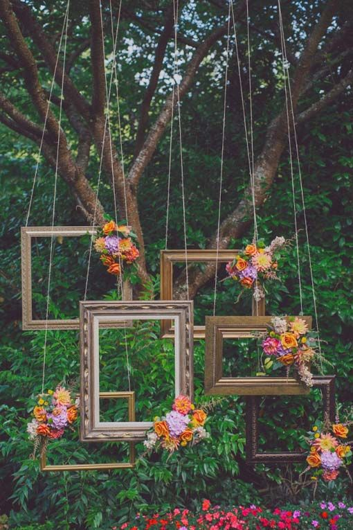 Vintage frames and bright blooms as wedding backdrop.