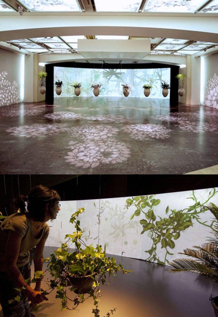 """Christa Sommerer e Laurent Mignonneau - """"Eau de Jardin"""" E' un'installazione interattiva che trasporta i visitatori nel mondo immaginario di giardini acquatici virtuali. Quando i visitatori si avvicinano verso le anfore, le piante catturano la presenza dei visitatori e utilizzando le tensioni che si verificano disegnano piante acquatiche virtuali sui grandi schermi di proiezione."""