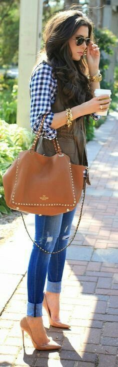 Gingham blouse,  khaki vest,  blue jeans and tan handbag
