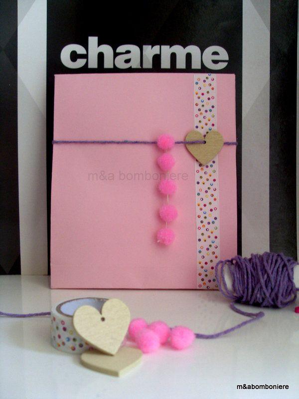Σε ροζ σακουλάκι, με πουά washi tape, ξύλινη καρδούλα, μωβ κορδονάκι και απαλά ροζ πομ πομ. Τιμή: 2,00 ευρώ.