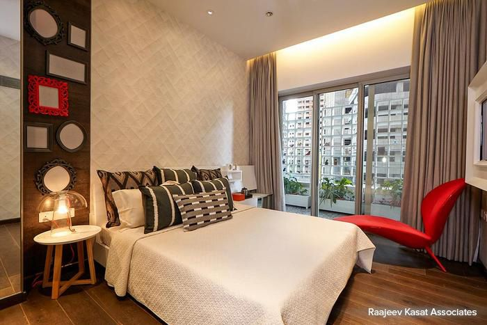 The interesting use of red furniture electrifies the otherwise calm and serene air in this bedroom #bedroom #homedecor #wooden #gray #contemporary Design Courtesy - Raajeev Kasat Associates, Mumbai