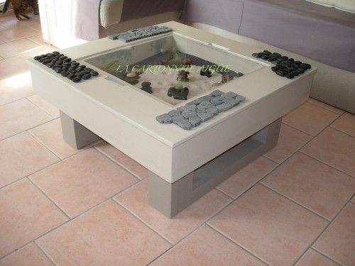 """Bonjour, Voici la table basse """"zen"""" en carton alvéolaire terminée et en situation. Elle a été peinte et vernie avec des produits éco-label, et des plantes épiphytes ont été mises dans le """"jardin"""". Grace à ses couleurs sobres et à la nuance claire de son..."""