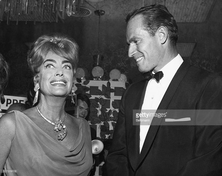 Actor Charlton Heston is admiring Joan Crawford's gorgeous tan and well he might. Joan spent two hard working weeks in a desert so she could dazzle her friends. Her days included swimming, riding, sun bathing and hiking.