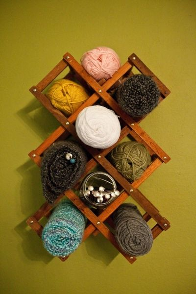 Use a small accordion wine rack to hold a few skeins of yarn on the wall