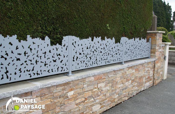 Une clôture très graphique grâce au parement en pierre du muret et par la découpe originale de l'aluminium.