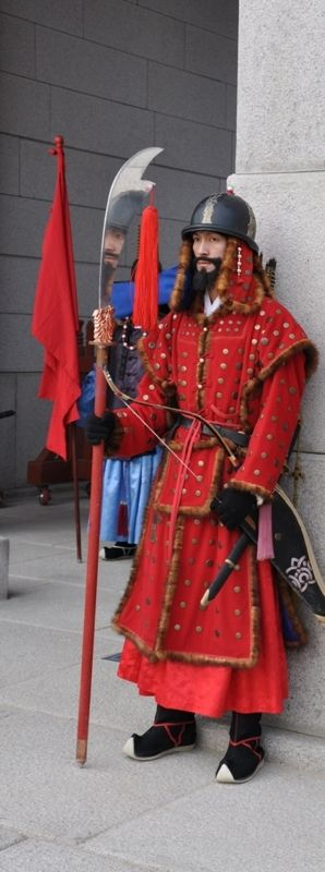 Korean Palace Guard: A guard at Seoul's Gyeongbokgung Palace stands menacingly guarding the main gate with his face reflecting in his shined metal knife.