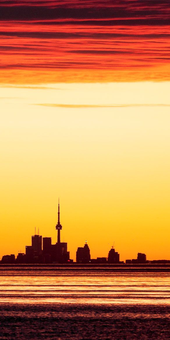Toronto Skyline at sunrise taken from the shore of Lake Ontario about 40 kilometers away from the CN Tower.