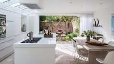 Белый кухонный остров в светлой кухне. Солнце падающее из верхних окон играет на гладкой поверхности кухонной столешницы. .