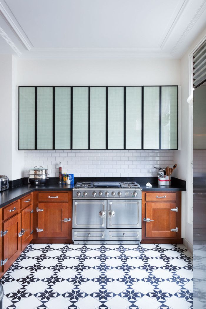 Great mix of traditional and modern with really cool harware. Warm wood, black metal, glass, and patterned tiles floor