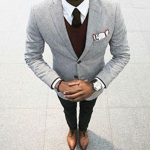 Acheter la tenue sur Lookastic: https://lookastic.fr/mode-homme/tenues/blazer-pull-a-col-en-v-chemise-de-ville/21042   — Chemise de ville blanche  — Cravate en tricot noir  — Pochette de costume blanc  — Pull à col en v bordeaux  — Blazer en laine gris  — Pantalon chino noir  — Chaussures richelieu en cuir brunes
