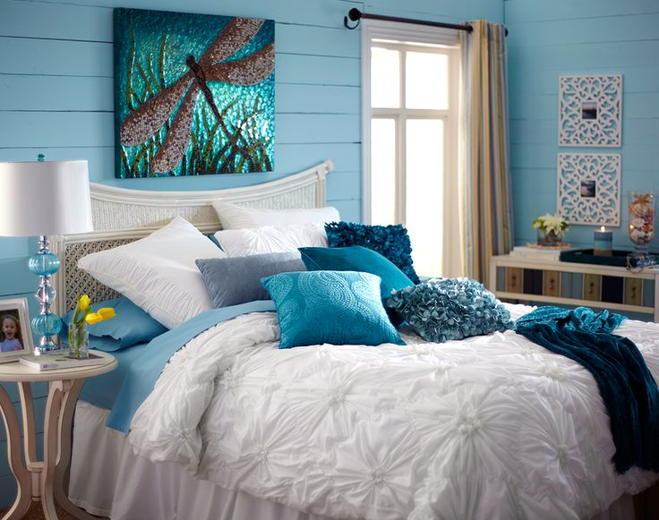 A blue lamp, blue pillows and blue walls inspire sweet dreams- perfect beach decor! Swap the dragonfly painting for something beachier!