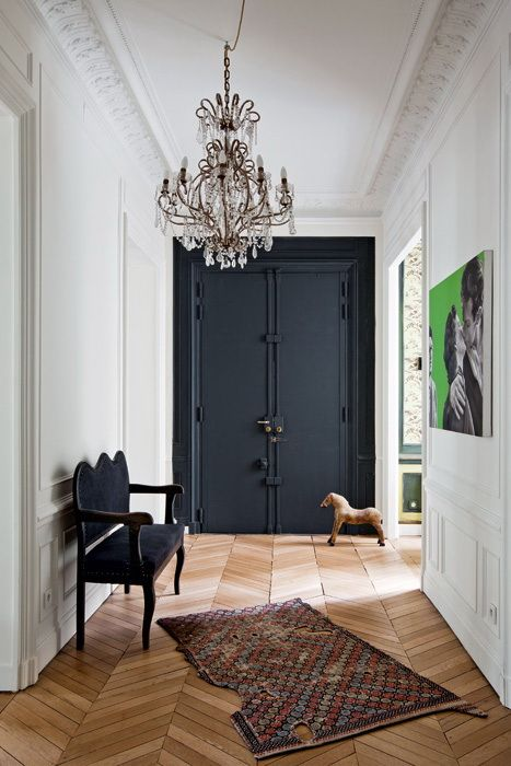 black accent wall/doors, chevron flooring, crystal chandelier, white walls and architectural mouldings, artful rug