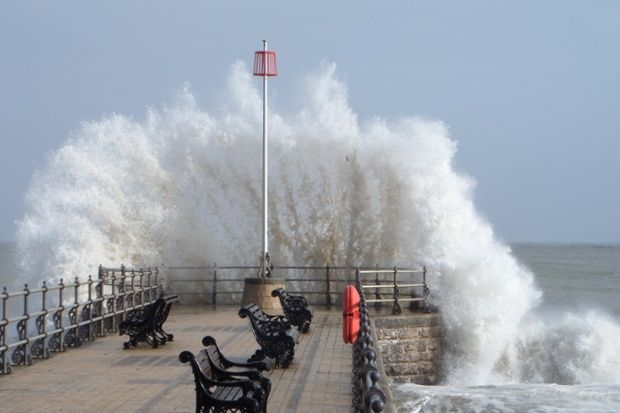 Waves breaking over the end of Banjo Jetty, the stone pier on Swanage beach, Dorset.