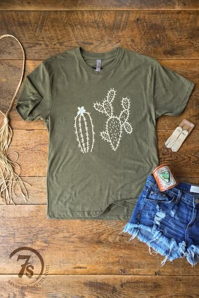Cactus graphic Tee. Ivory and cream cacti graphic. Light olive green tri-blend soft t-shirt. Unisex sizing. Fit is true to a loose fitting women's t-shirt i.e. Small fits size 3-5. Shown styled with the Houston Necklace, Saydie Earrings and Ketoh Cuff. Get custom High Quality Women shirts at an affordable price. Order now!