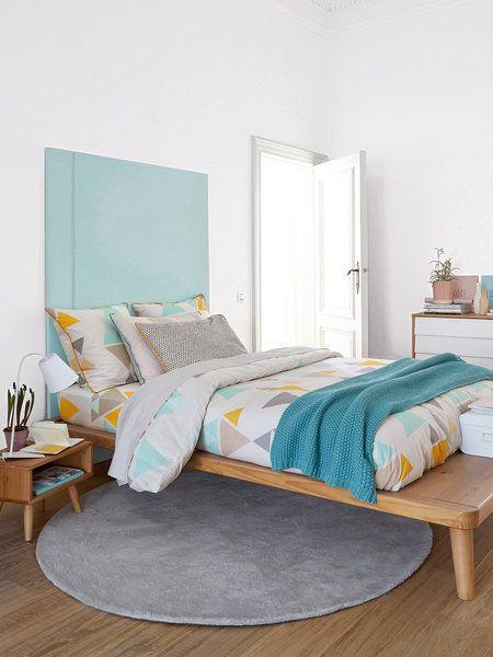 Dormitorio decorado en madera y tonos pastel con cabecero azul