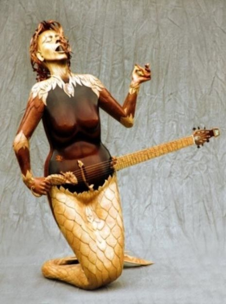 The 'Mermaid' guitar. Built by world-renowned Luthier, Andy Mason.    Andy Mason, the artist and musician responsible for this gorgeous yet completely bizarre fully-functional guitar in the shape of a mermaid, built his first guitar in 1967 using whatever materials he was able to find in his father's garage. And ever since the incredibly talented luthier (the proper title for person or craftsman who makes stringed instruments), has made everything from lutes to mandolins