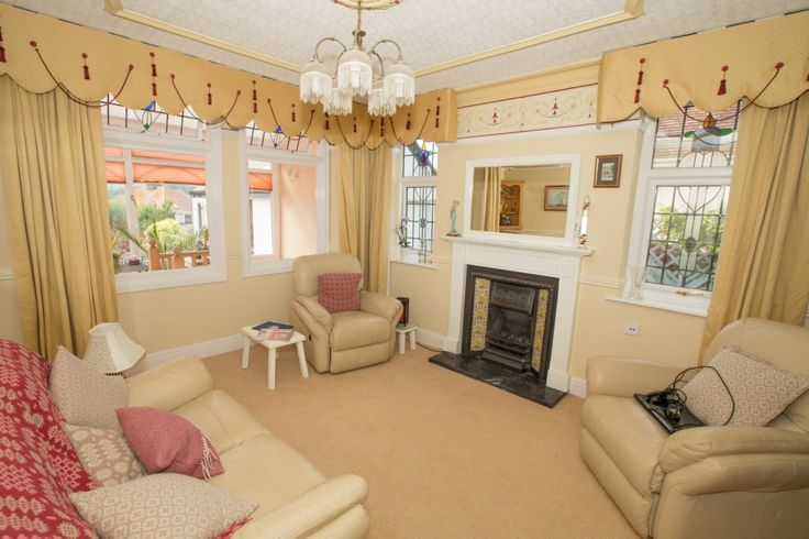 Lounge with views through Conservatory to mountains, vintage fireplace with daffodil tiles, stained glass windows x 2 access through to sitting room