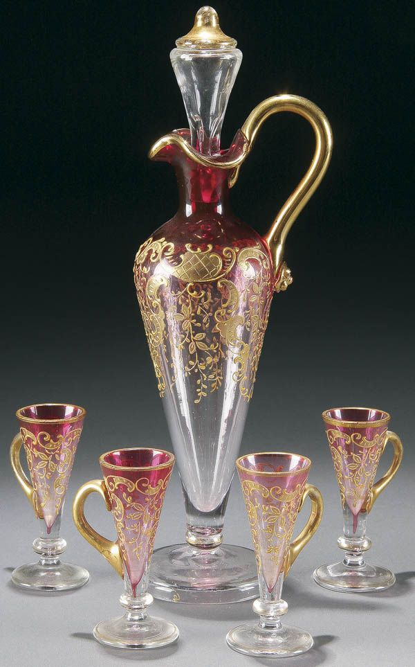 A BOHEMIAN ENAMELED GLASS CORDIAL SET 5-piece, early 20th century. Comprising a footed ewer with stopper and 4 matching handled footed cordials in Rubina glass.