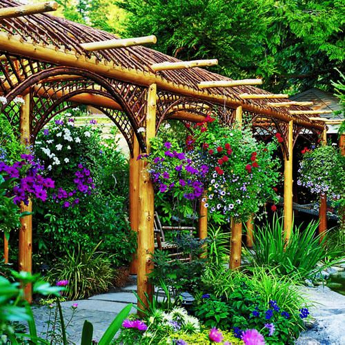 This is a gorgeous rustic arbor pathway! The lush landscaping, array of bright flowers and a comfortable custom bench make this outdoor space a spectacular oasis. | Caption by Jenn Brown: Gardens Ideas, Hanging Plants, Gardens Landscape, Rustic Arbors, Mediterranean Garden, Gardens Shades, Flowers Baskets, Beautiful Arbors, Hanging Baskets