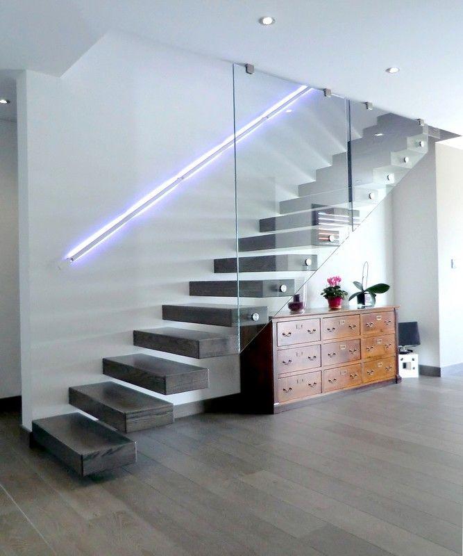 Escalier Ego, marches en console sur mur en béton banché, frêne teinté vernis et garde-corps tout verre.