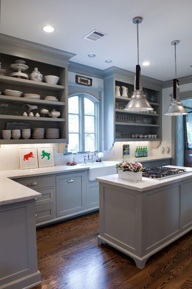 Серый кухонный гарнитур с белыми мраморными столешницами, фермерская раковина, серые стены, белая и стеклянная посуда – оформление современной кухни в Хьюстоне. Окно напротив рабочей области и два вида источников искусственного освещения обеспечивают кухню необходимым светом
