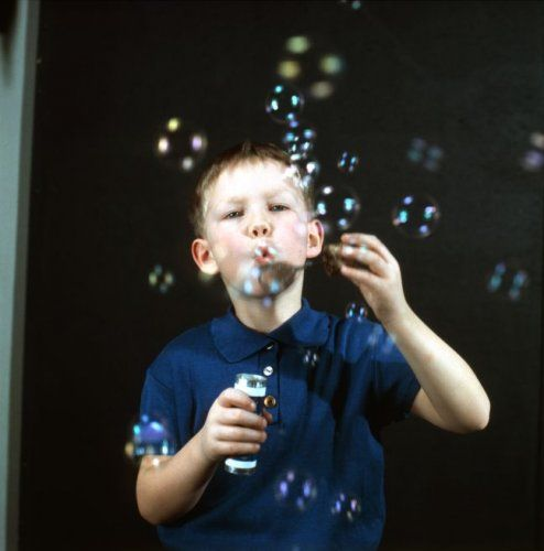 Kinderen, spelen, bellen blazen. Jongen druk bezig met het blazen van zeepbellen. Studio-opname, Nederland, 1968.