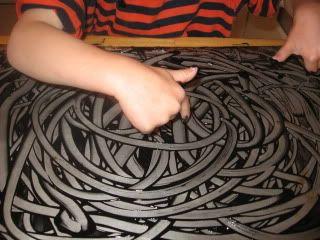 Pintura de dedos invertida. Rellenar con pintura negra, dibujar con el dedo, poner otro papel encima antes de que seque.