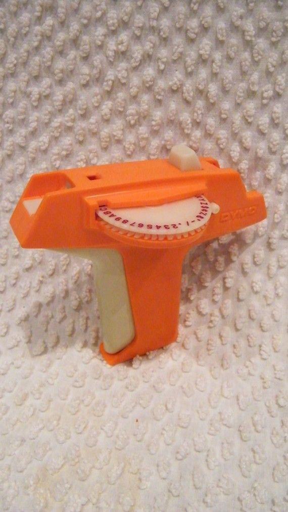 Essa maquininha de plástico era uma impressora. Usava-se uma fita adesiva de plástico de várias cores, e escrevia nelas. Geralmente era para identificar pastas de arquivos, ou objetos de escritória e na escola...