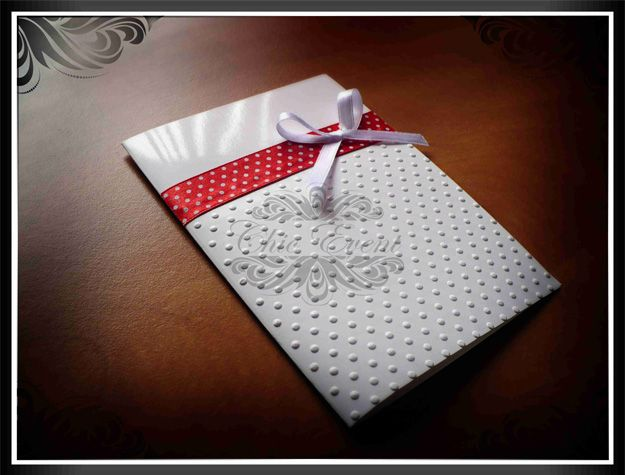 Wedding invitation card on colored and embossed cardboard with colored ribbons.