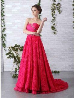 Vestido de fiesta en color rosa fucsia con corte en A y escote palabra de honor con escote corazón. Parte superior drapeada y la inferior relieve de flores en un manto.