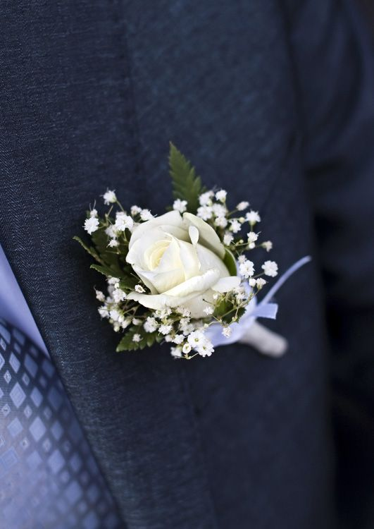With baby's breath and greenery for groom, with only greenery for the other men