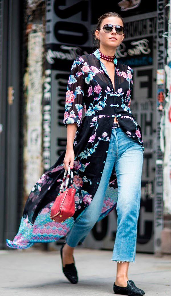 Street style look com blusa esvoaçantes estampada, jeans claro e mule preta, provando que para ser estilosa o salto não é obrigatório.