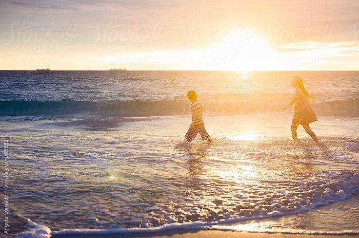 Boy and girl splashing at the beach by Angela Lumsden