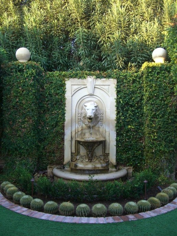 Old World style lion head fountain surrounded
