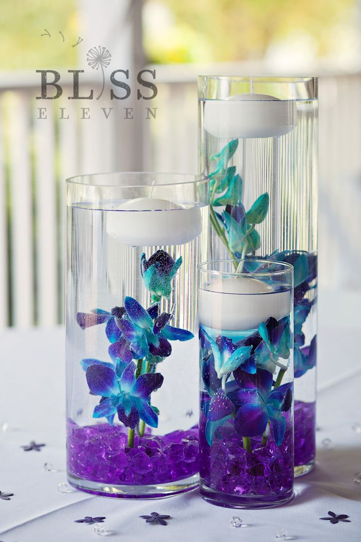 A centerpiece collection of amazing underwater Blue bomb dendrobium orchids accented by pure white floating candles and purple gems ... breathtaking! by Jenny Thomasson AIFD CFD of Stems Florist - St. Louis, MO Photos by Bliss Eleven #underwater #centerpiece #orchids